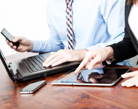 Um homem utilizando Notbook e uma Mulher utilizando um iPad